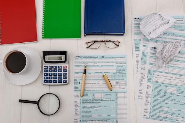 テーブルに電卓とコーヒーを置いた納税申告書