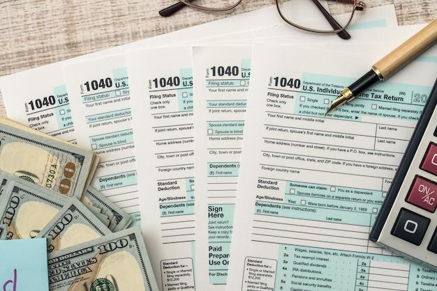 달러, 계산기, 펜이 있는 세금 양식