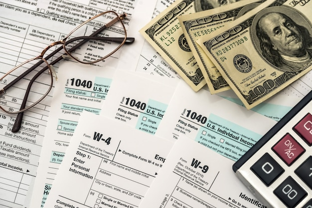 Tax form with dollar, calculator and pen