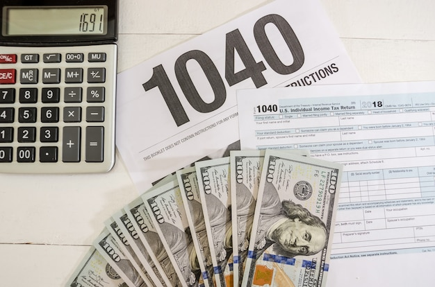 Tax forms 1040 and calculator with dollars