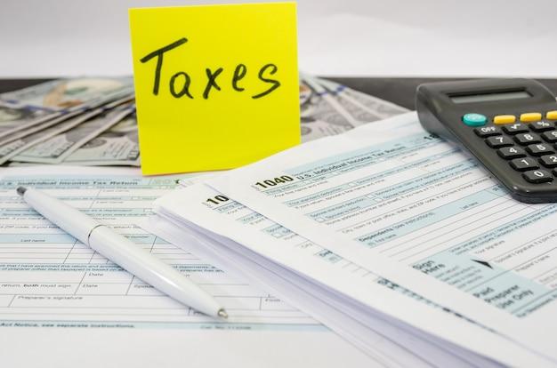 Налоговая форма 1040 с калькулятором и ручкой на столе