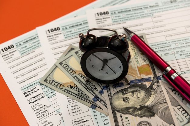 Tax forms 1040 with clock pen and dollar bills