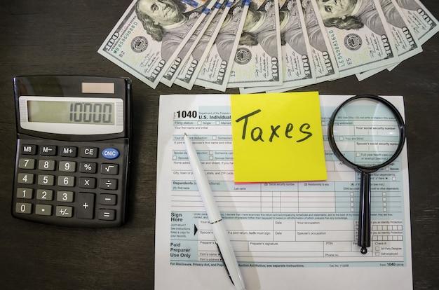 Налоговая форма 1040 с долларовым калькулятором и ручкой