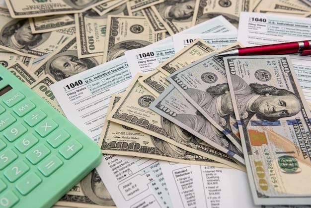 4月に記入するためのドルと計算機を備えた納税申告書1040。税金の概念。