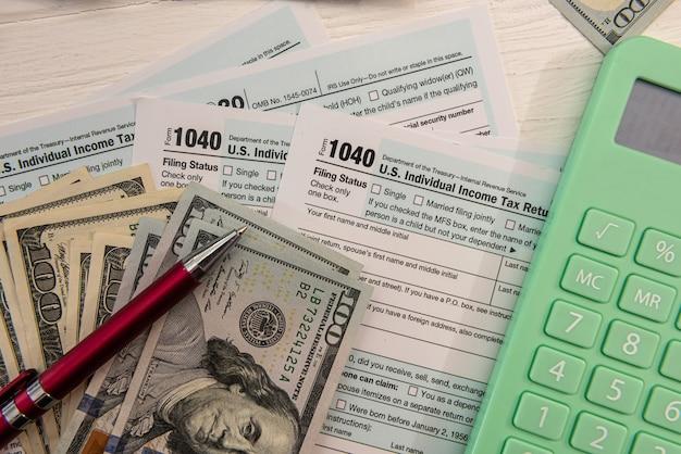 세금 양식 1040에는 달러와 4월에 작성하기 위한 계산기가 포함되어 있습니다. 세금 개념입니다.