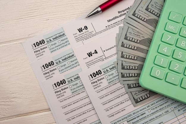 세금 양식 1040에는 4월에 작성하기 위한 달러와 계산기가 포함되어 있습니다. 세금 개념입니다.