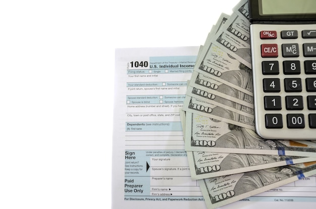 Tax forms 1040 with dollars and calculator on white background
