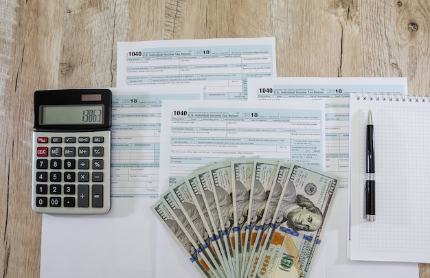 Tax forms 1040 with dollars and a calculator on a wooden table