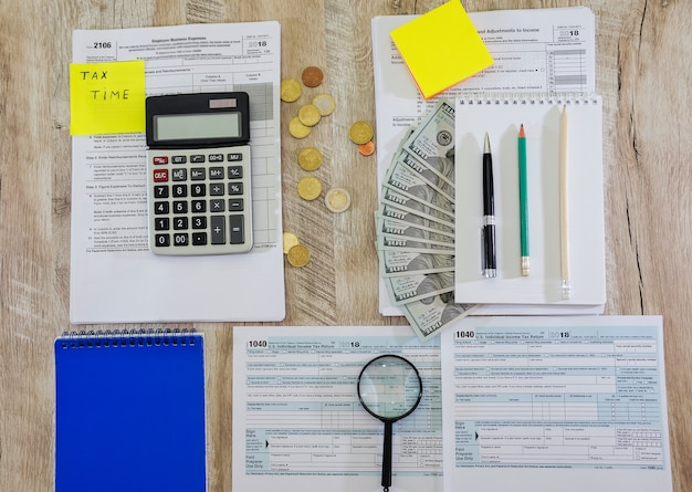 Tax forms 1040 with stationery on the table