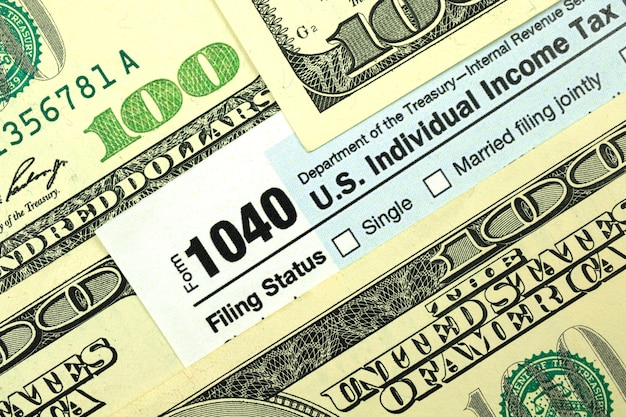 Tax forms among hundred dollar bills close-up, concept of tax season, time to pay