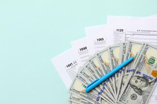 Tax forms lies near hundred dollar bills and blue pen