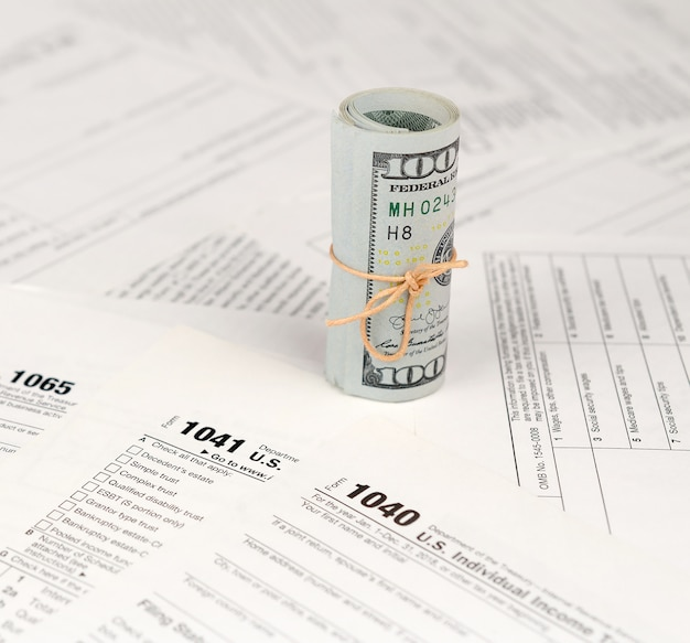 Tax forms lies near roll of hundred dollar bills. income tax return