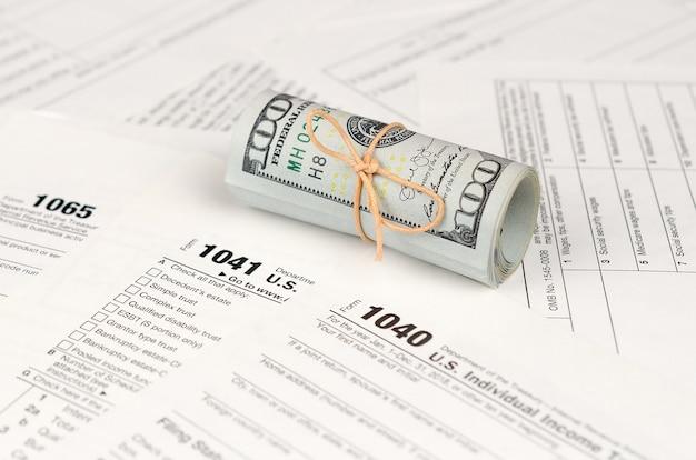 Tax forms lies near roll of hundred dollar bills