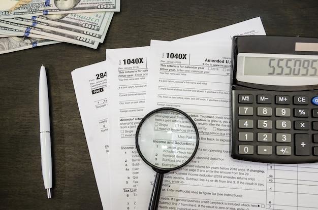 Налоговые формы с лупой и калькулятором