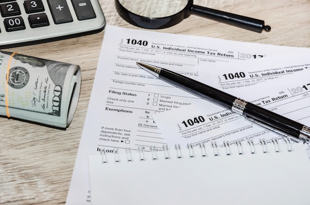 Tax forms with  pen and  dollars