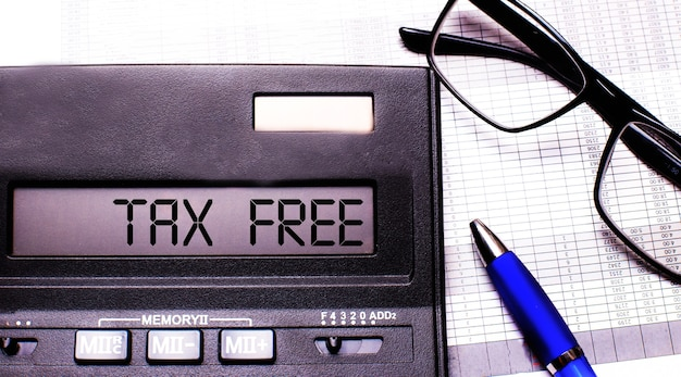 Tax free is written in the calculator near black-framed glasses and a blue pen.