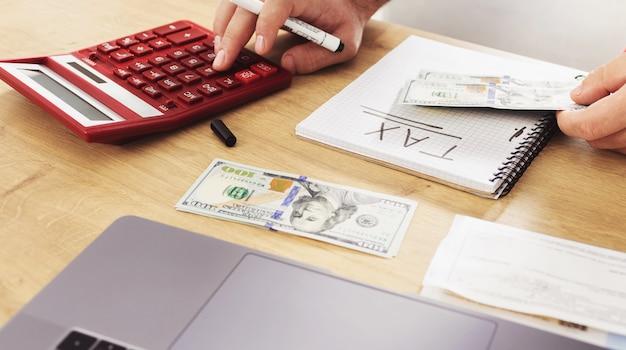 Концепция уплаты налогов деловой человек, использующий калькулятор для расчета налогов
