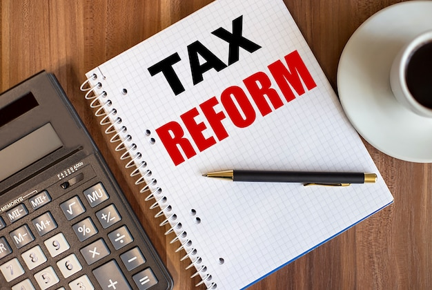 Tax reform written in a white notepad near a calculator and a cup of coffee on a dark wooden background