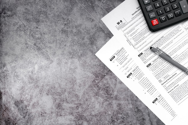 Tax relief and tax forms with a signature pen and a calculator to calculate taxes on a gray surface