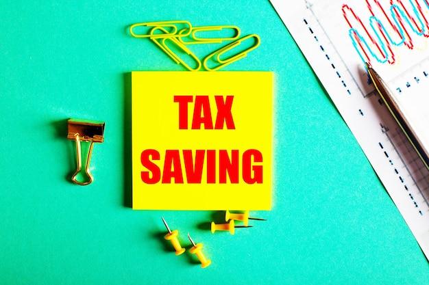Tax savingは、グラフと鉛筆の近くの緑の表面にある黄色のステッカーに赤で書かれています