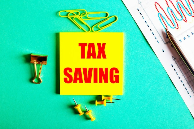 Tax saving is written in red on a yellow sticker on a green surface near the graph and pencil