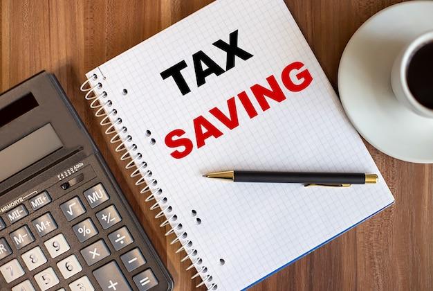 電卓の近くの白いメモ帳と暗い木製の背景に一杯のコーヒーで書かれた税金の節約