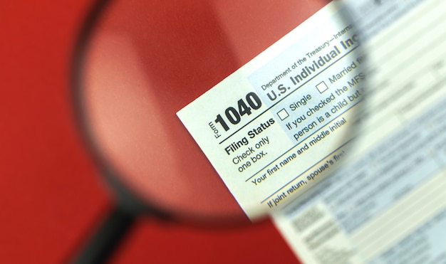Tax season with magnifying glass, 1040 tax form background, red office desk top view photo