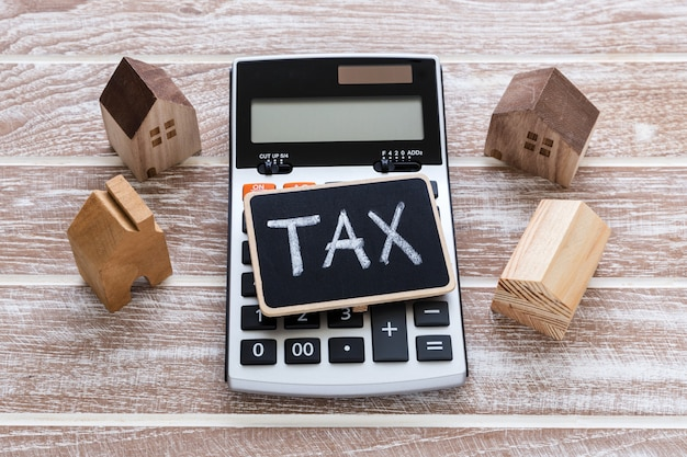 Tax sign on calculator with house model