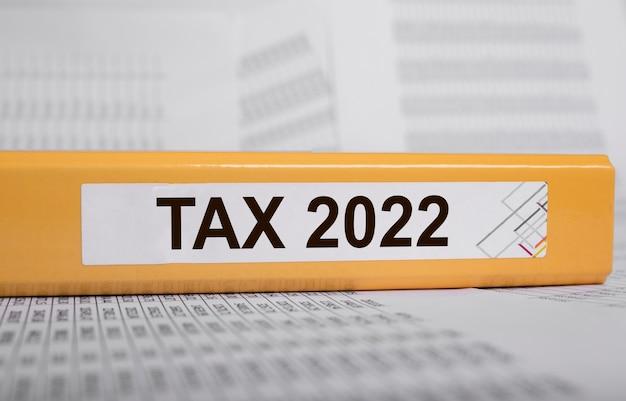 Слово налоговой системы налогообложения на желтой папке на документах