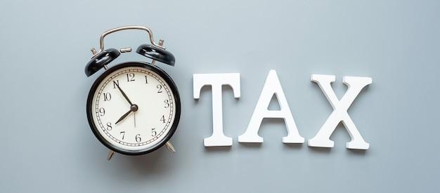 세금 텍스트 및 알람 시계 투자 및 세금 개념