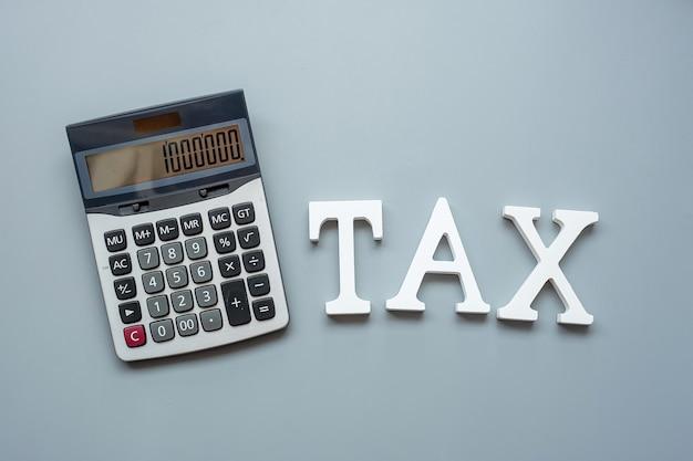 회색 계산기로 세금 텍스트. 세금 개념에 대한 투자 및 시간