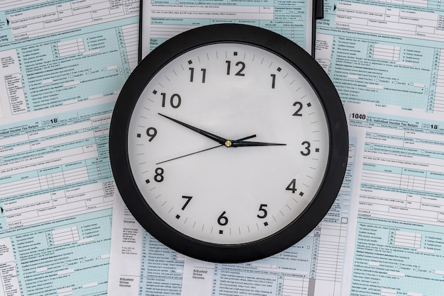 Tax time concept, clock at 1040 tax form