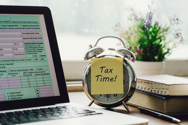 Tax time concept tax time on a postit on alarm clock and individual income tax return form online
