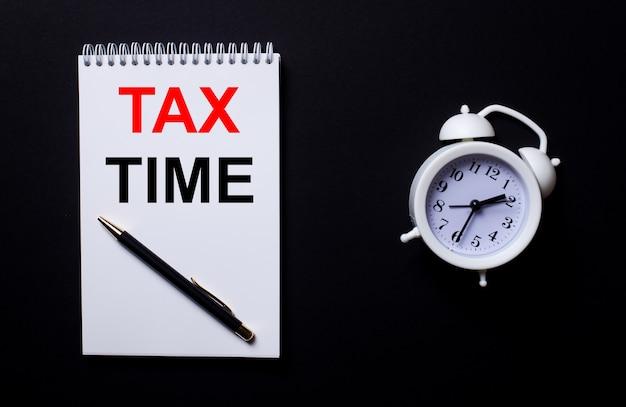 Налоговое время написано в белом блокноте возле белого будильника на черном фоне