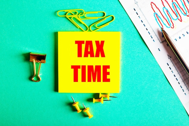 Tax time is written in red on a yellow sticker on a green background near the graph and pencil