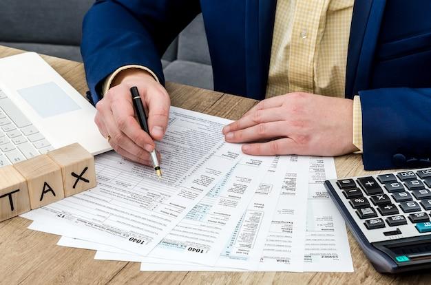 課税時間。 1040フォームに記入する男性の手