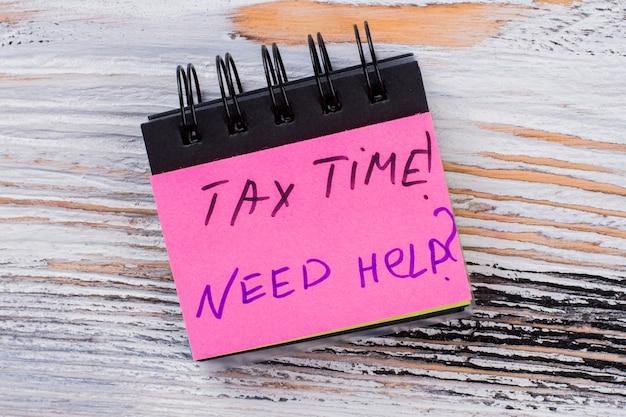 ミニメモ帳の紙に税の時間メッセージ。あなたの税金について助けが必要です。背景に白い木。