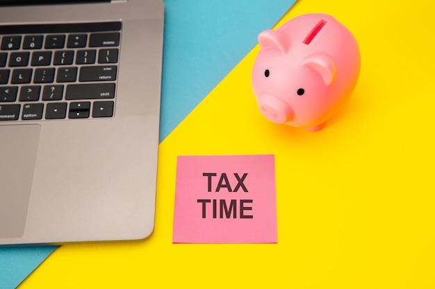 Налоговое время - уведомление о необходимости подачи налоговой декларации, налоговой формы на рабочем месте бухгалтера. копилка в розовом цвете с ноутбуком и канцелярскими принадлежностями на красочном