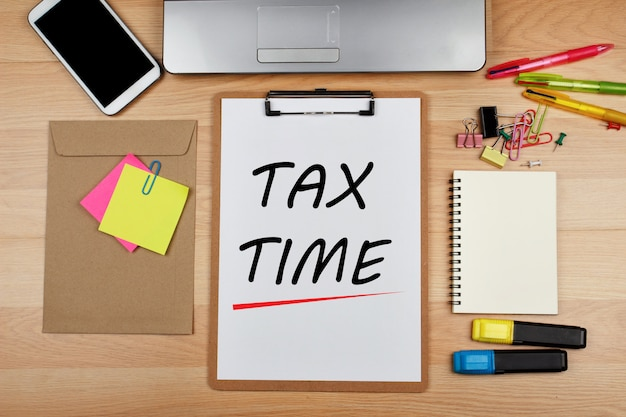 Tax time text on paper white sheet with office supplies on wooden desk
