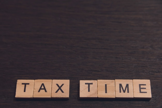 Tax time with wooden alphabet blocks on dark plank wooden with copy space