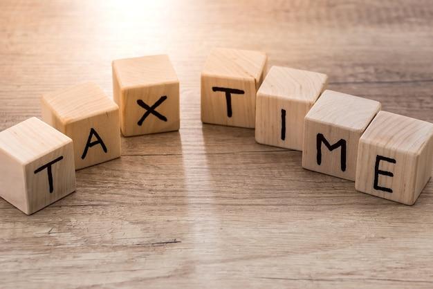 木製の机の上の木製の立方体との課税時間