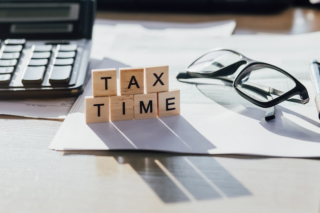 納税申告書、グラス、電卓付きのタックスタイム木製手紙