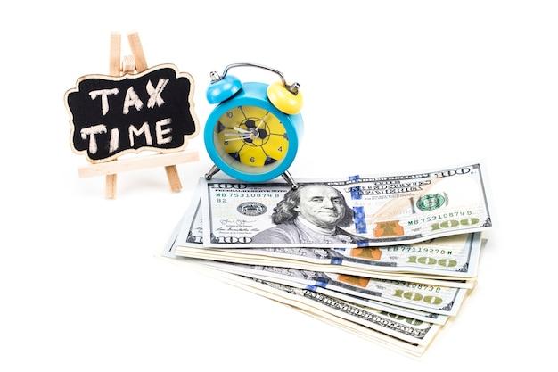 흰색 바탕에 돈과 알람 시계가 있는 칠판에 쓰여진 세금 시간.