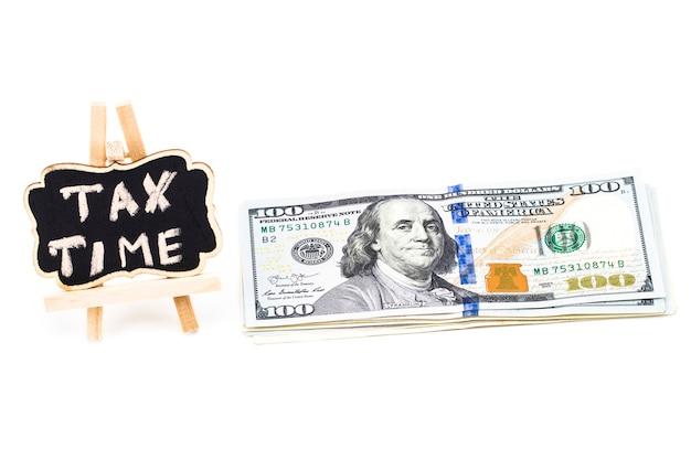 흰색 바탕에 돈으로 칠판에 쓰여진 세금 시간.