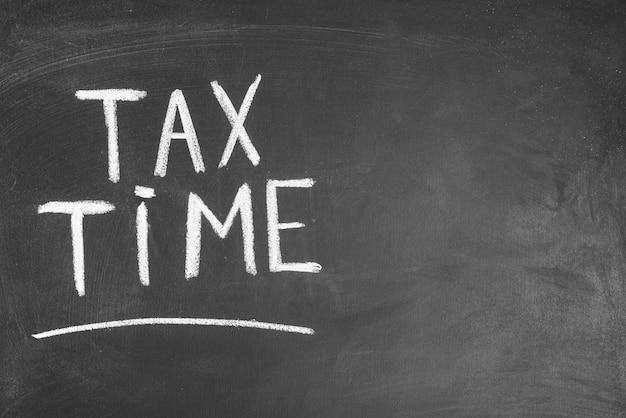 黒のバックボードに税の時間書かれたテキスト