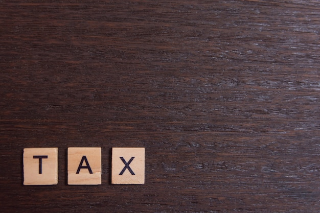 Tax with wooden alphabet blocks, on dark plank wooden with copy space
