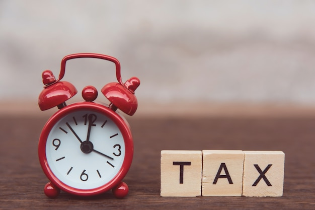 Tax with wooden alphabet blocks, red alarm clock on dark plank wooden with copy space