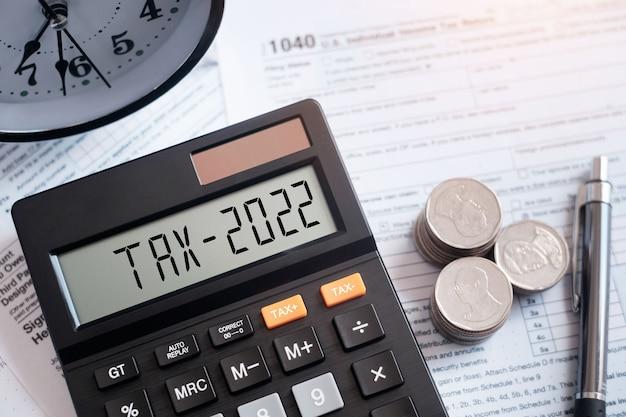 電卓の税の言葉と2022年の数字。 1040税務フォームのペンとコイン。営業税。 2022年の新年の税の概念。