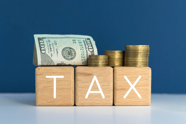 Tax word on wood cubes, coins and 100 hundred dollar. american currency. money and finances.