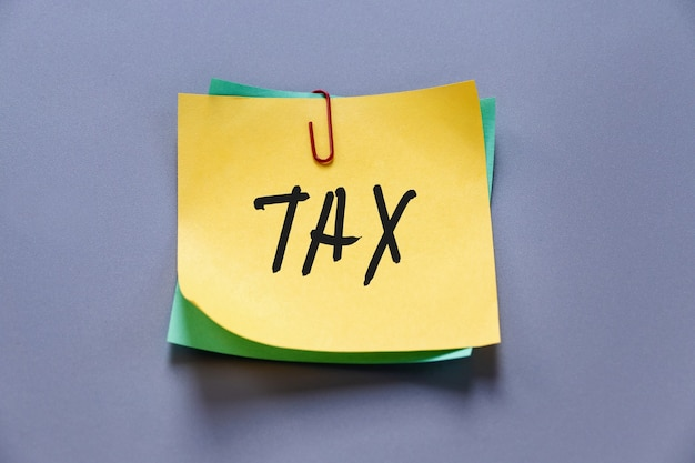 Tax word on yellow paper note